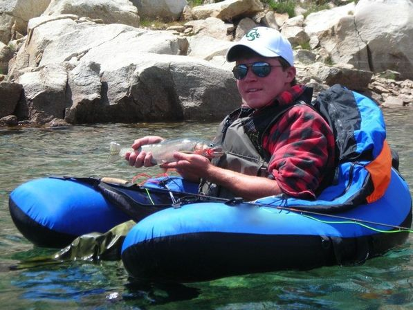 ultralight float tube for fly fishing in high mountain lake with young man holding trout he caught